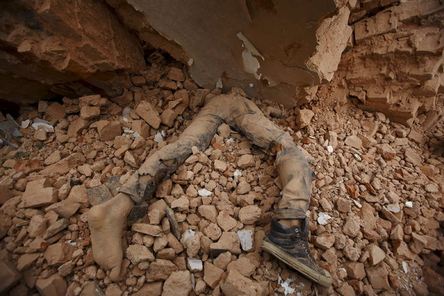 A body of a victim lies trapped in the debris after an earthquake hit, in Kathmandu, Nepal April 25, 2015. (Photo by Navesh Chitrakar/Reuters)