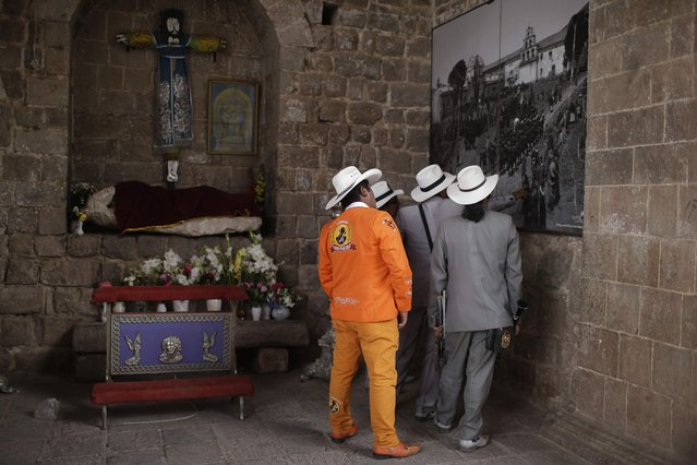 In this Sunday, August 5, 2018 photo, members of the Majestic Union band look at a 1930's Martin Chambi photo, displayed on a facade of the Almudena Temple, as they wait to take part in a religious procession honoring Our Lady of Copacabana, in Cuzco, Peru. Chambi is known for photographing the elite members of Cuzco's society, as well as extensively documenting the Peruvian indigenous culture. (Photo by Martin Mejia/AP Photo)