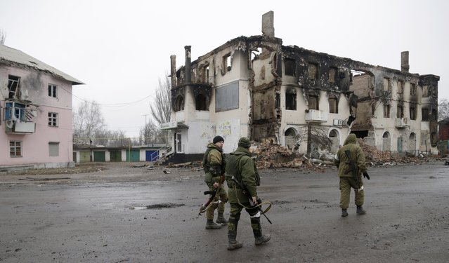 A  pro-Russian rebels walk past a destroyed building in the town of Vuhlehirsk, Ukraine, Friday, February 6, 2015. (Photo by Petr David Josek/AP Photo)