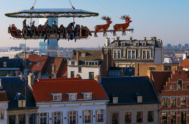 "Guests enjoy a dinner at the table ""Santa in the sky"" lifted by a crane and elevated at 50 meters in the air and decorated to match the appearance of a ""Santa Sleigh"", as part as the Christmas festivities in Brussels, Belgium, November 25, 2016. (Photo by Yves Herman/Reuters)"