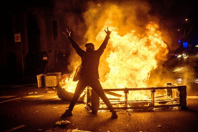 """A protester poses for a photo in front of a burning barricade in Barcelona, Spain on February 17, 2021 as a protest following the imprisonment of rapper """"Pablo Hasel"""" convicted to jail for glorifying terrorism and insulting Spain's former king in lyrics turns into riots for a second night. (Photo by Matthias Oesterle/ZUMA Wire/Rex Features/Shutterstock)"""
