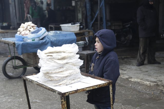 A boy waits for customers as he sells bread during cold weather in the rebel-controlled area of Maaret al-Numan town in Idlib province, Syria, January 4, 2016. (Photo by Khalil Ashawi/Reuters)