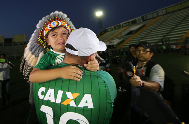 A fan of Chapecoense soccer team and his son react at the Arena Conda stadium in Chapeco, Brazil, November 29, 2016. (Photo by Paulo Whitaker/Reuters)