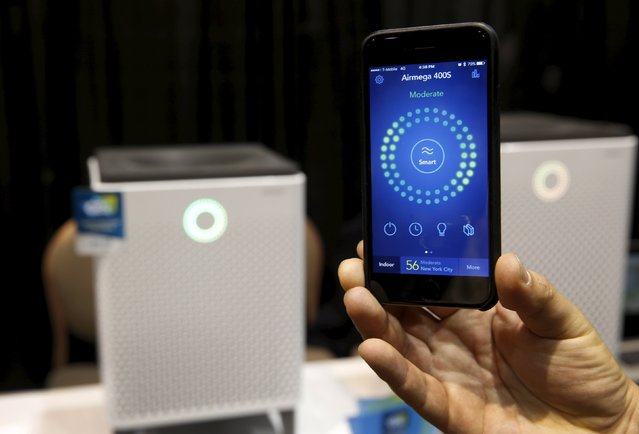 """A smartphone receives real-time information on air quality from an Airmega air purifier from Coway during """"CES Unveiled,"""" a preview event of the 2016 International CES trade show, in Las Vegas, Nevada January 4, 2016. The WiFi-enabled, smart air purifiers from South Korea range in price from $749.00-$849.00 depending on the size. (Photo by Steve Marcus/Reuters)"""