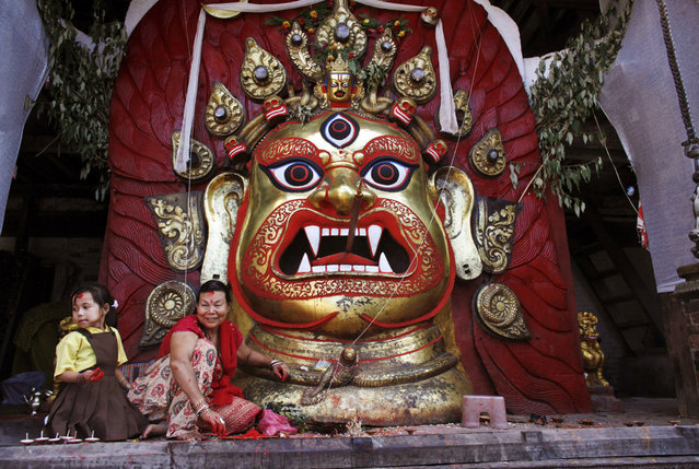 A Nepalese woman and a girl sit in front of a statue of Hindu deity Swet Bhairav during the last day of the week-long Indra Jatra festival in Katmandu, Nepal, Monday, September 16, 2013. The festival marks the end of the monsoon season and beginning of autumn. (Photo by Niranjan Shrestha/AP Photo)