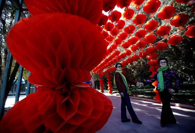 Visitors pose for a picture next to paper lanterns celebrating the Chinese New Year celebrations at Ditan Park, also known as the Temple of Earth, in Beijing February 18, 2015. (Photo by Kim Kyung-Hoon/Reuters)