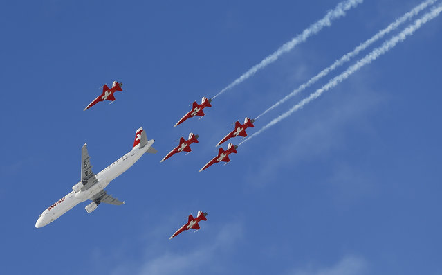 Members of the Swiss aerobatic team Patrouille Suisse fly in formation with a Swiss Airbus A 320 over the men's Alpine Skiing World Cup Super Combined race in Wengen, Switzerland January 15, 2016. (Photo by Ruben Sprich/Reuters)