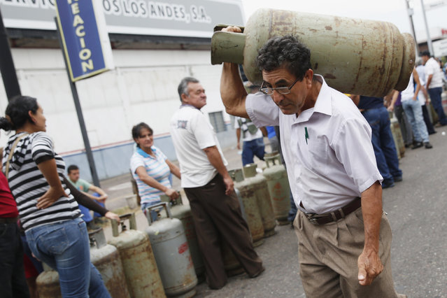 A man carrying a gas cylinder walks past a line of people queuing up to buy gas cylinders at a distribution point of Venezuelan state-owned oil and natural gas company PDVSA in San Cristobal, February 28, 2014. (Photo by Carlos Garcia Rawlins/Reuters)