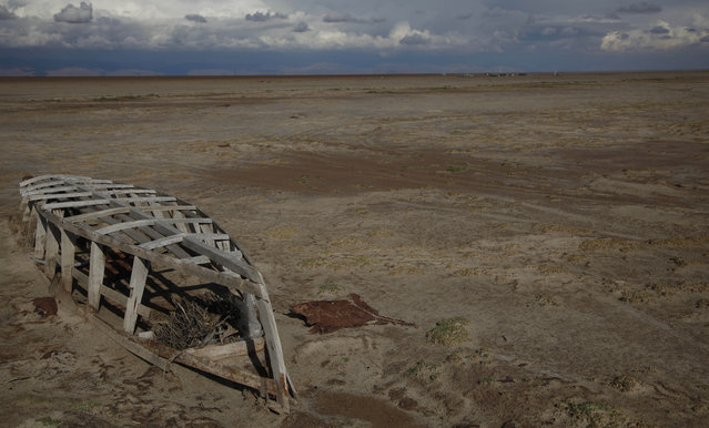 In this January 12, 2016 photo, an abandoned boat lies on the dried up lake bed of Lake Poopo, on the outskirts of Untavi, Bolivia. Environmentalists and local activists say the government mismanaged the lake's fragile water resources and ignored rampant pollution from mining, Bolivia's second export earner after natural gas. (Photo by Juan Karita/AP Photo)
