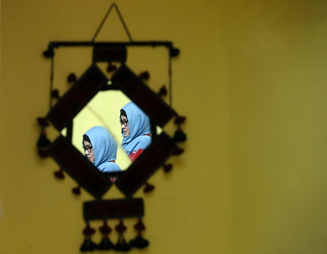 Masooma Alizada, a member of Afghanistan's Women's National Cycling Team is reflected in a mirror at a house in Kabul February 20, 2015. Afghanistan's Women's National Cycling Team has been breaking new ground for women's sports and pushing the boundaries of what is – and is not – acceptable for young women in the conservative Muslim country.  (Photo by Mohammad Ismail/Reuters)