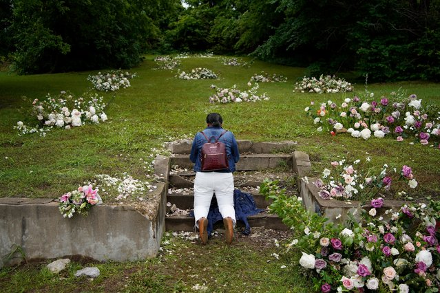 """Linda Porter of Birmingham, Ala., kneels at a makeshift memorial of flowers for the Tulsa Race Massacre at stairs leading to a now empty lot near the historic Greenwood district during centennial commemorations of the massacre, Tuesday, June 1, 2021, in Tulsa, Okla. """"We came to remember"""", said Porter, who came to Tulsa for the centennial commemorations. (Photo by John Locher/AP Photo)"""