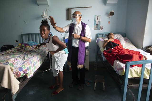 Father Felix Mendoza, a Venezuelan Catholic priest, center, prays over a woman who cries, saying she is in physical pain, at a public hospital in Caracas, Venezuela, Tuesday, May 11, 2021, amid the new coronavirus pandemic. Father Felix has been visiting patients at the hospital to comfort the sick, for the last 20 years. (Photo by Ariana Cubillos/AP Photo)