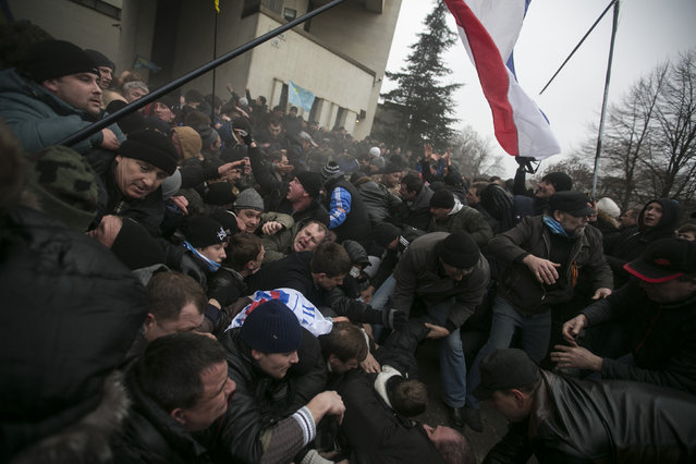 Ukrainian men help pull one another out of a stampede as a flag of Crimea is seen during clashes at rallies held by ethnic Russians and Crimean Tatars near the parliament building in Simferopol February 26, 2014. (Photo by Baz Ratner/Reuters)