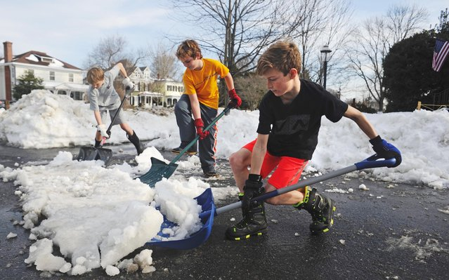 As temperatures push into the upper 50s, from left, Sam DuMont, Jake Wack, and Luke DuMont shovel a patch of snow and ice along Washington Avenue in Fredericksburg, Va., Tuesday, January 26, 2016. The three youths have spent their snow days shoveling snow for homeowners in town. The three let their customers determine how much money to pay them. (Photo by Peter Cihelka/The Free Lance-Star via AP Photo)