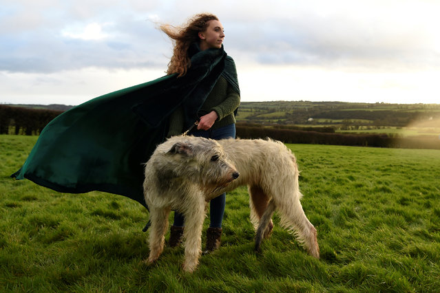 Rebecca Smith poses for a photograph during winter solstice with her Irish Wolfhound dog called Amazing Grace at the 5000 year old stone age tomb of Newgrange (not in view) in the Boyne Valley at sunrise in Newgrange, Ireland, December 21, 2016. (Photo by Clodagh Kilcoyne/Reuters)