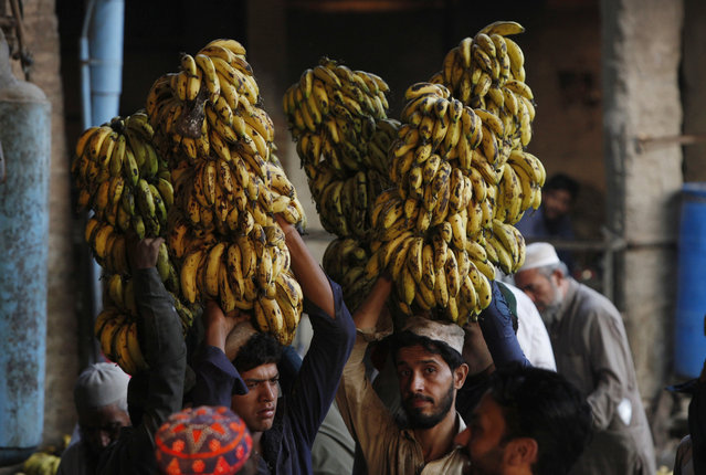In this Wednesday, September 12, 2018, file photo, vendors carry banana on their heads at a fruit and vegetable market in Peshawar, Pakistan. Pakistan says it will seek a bailout loan from the International Monetary Fund to address a mounting balance of payments crisis, Finance Minister Asad Umar said Monday. (Photo by Muhammad Sajjad/AP Photo)
