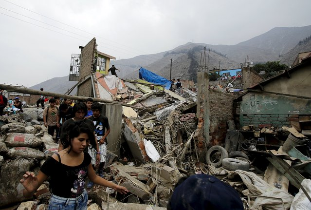 A woman walks pasts debris of houses after a massive landslide in Chosica, March 24, 2015. (Photo by Mariana Bazo/Reuters)