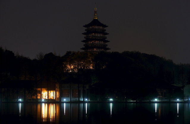 Leifeng Pagoda is seen behind the West Lake during Earth Hour in Hangzhou, Zhejiang province, March 28, 2015. (Photo by Chance Chan/Reuters)