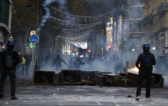 Demonstrators stand behind a burning barricade during clashes, Saturday, December 8, 2018 in Marseille, southern France. The rumble of armored police trucks and the hiss of tear gas filled central Paris on Saturday, as French riot police fought to contain thousands of yellow-vested protesters venting their anger against the government in a movement that has grown more violent by the week. (Photo by Claude Paris/AP Photo)