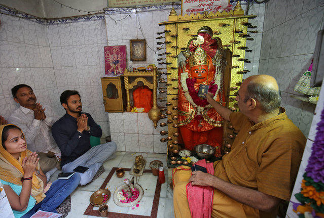 A family prays with their passports in front of the idol of the Hindu god Hanuman as they seek blessings to acquire visa to fulfill their dream of going abroad, at Visa Hanuman Temple, in Ahmedabad, December 4, 2018. (Photo by Amit Dave/Reuters)