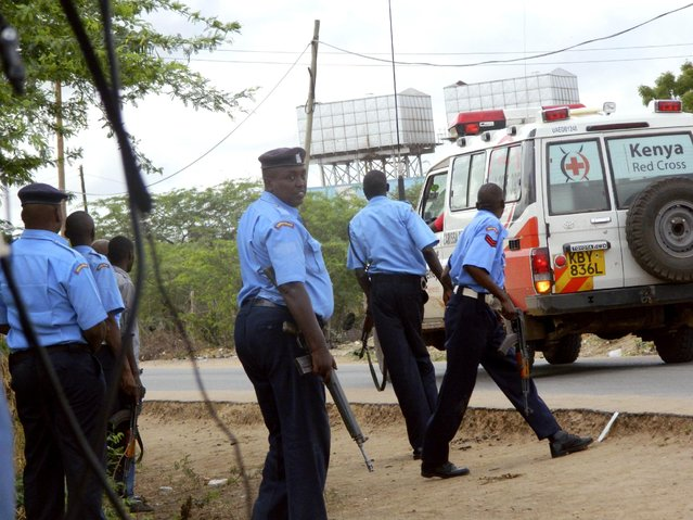 Kenyan police officers take positions outside the Garissa University College as an ambulance carrying the injured going to a hospital, during an attack by gunmen in Garissa, Kenya, Thursday, April 2, 2015.  Gunmen attacked the university early Thursday, shooting indiscriminately in campus hostels. Police and military surrounded the buildings and were trying to secure the area in eastern Kenya, police officer Musa Yego said. (Photo by AP Photo/Stringer)