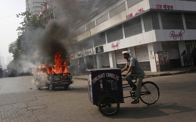 A vendor selling candles rides his bicycle past a burning taxi along a road in Mumbai December 3, 2013. No casualties were reported, and the cause of the fire was not known. (Photo by Danish Siddiqui/Reuters)