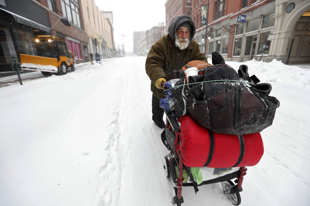 James Spanos pushes a cart of his belongings on a snow-covered street during a winter storm, Sunday, January 20, 2019, in Portland, Maine. Scarves, hoods and gloves were necessary for New England residents venturing outdoors as the region endures a storm that can dump up to 18 inches of snow. (Photo by Robert F. Bukaty/AP Photo)