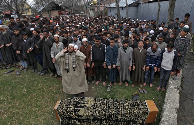 Kashmiris perform funeral prayers in front of a coffin containing the body of Mushatq Ahmad Wani, an Indian policeman, in Arigam, south of Srinagar April 6, 2015. (Photo by Danish Ismail/Reuters)