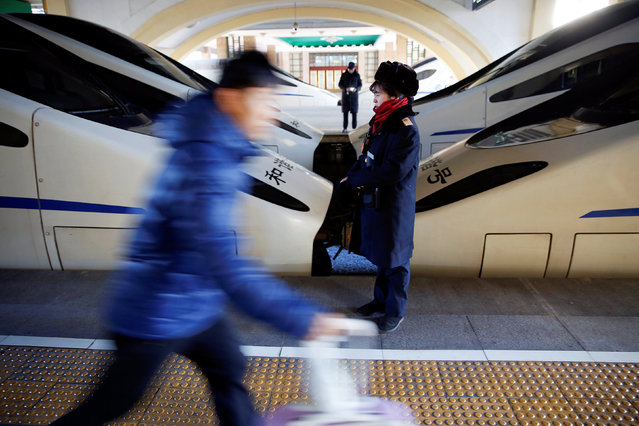 A passenger rushes past a railway worker at the Beijing Railway Station in central Beijing, China January 13, 2017 as the annual Spring Festival travel rush begins ahead of the Chinese Lunar New Year. (Photo by Damir Sagolj/Reuters)