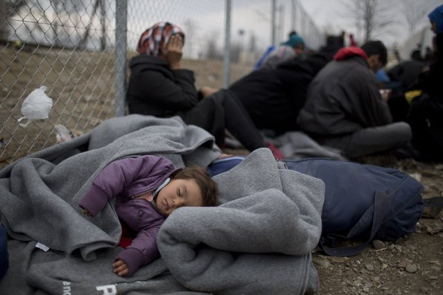 A children sleeps as refugees wait to be allowed to cross the the Greek-Macedonian border near the northern Greek village of Idomeni , Wednesday, February 24, 2016. The Greek interior ministry said about 12,000 people have been stranded in Greece since neighbor Macedonia began turning Afghan immigrants away at the border and slowing the number of crossings for others heading to central and northern Europe. (Photo by Petros Giannakouris/AP Photo)