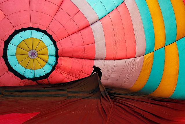 A worker adjusts the interior of a hot air balloon before its take off on the banks of the river Ganges in Allahabad, India January 17, 2017. (Photo by Jitendra Prakash/Reuters)