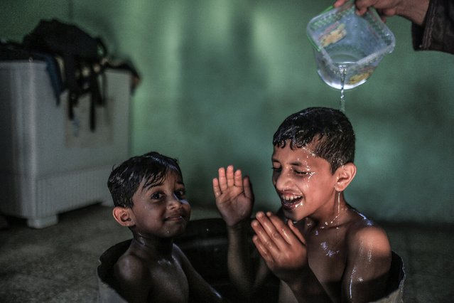 A Palestinian mother washes her sons in their house during hot weather in a slum on the outskirts of Khan Younis refugee camp, Gaza Strip, 04 August 2021. (Photo by Mohammed Saber/EPA/EFE)