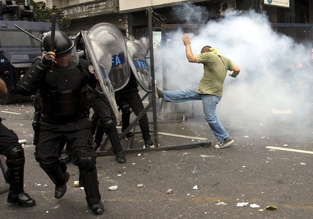 A student of the Buenos Aires University Union Federation (FUBA) kicks a barrier in front of the Congress in Buenos Aires, in this December 14, 2009 file photo, amid clashes with riot police during a protest staged to avoid an assembly to elect the new rector of the university. (Photo by Joaquin Salguero/Reuters)