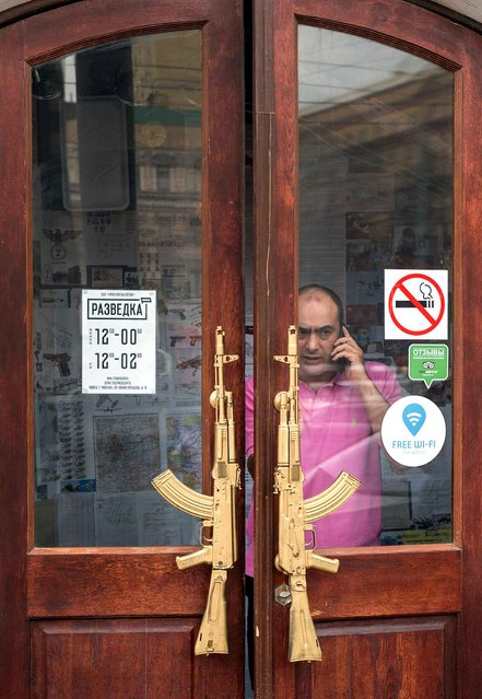 A man comes out of restaurant doors decorated with Kalashnikov's AK-74 assault rifles in downtown Moscow on February 25, 2016. (Photo by Dmitry Serebryakov/AFP Photo)