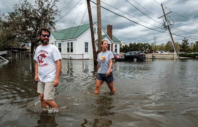 Two people walk through a flooded neighborhood from Hurricane Ida in Narco, Louisiana, USA, 30 August 2021. Hurricane Ida made landfall as a Category 4 storm bringing damaging winds and rain to southern Louisiana, knocking out power to more than one million people and flooding neighborhoods. At least one person was reported killed by the passing of the hurricane. (Photo by Dan Anderson/EPA/EFE)