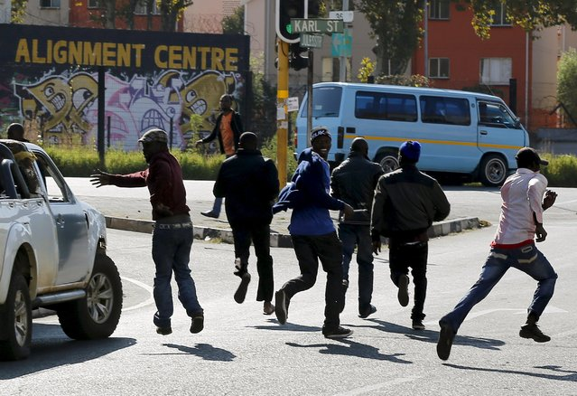 African immigrants run as they are dispersed by police officers in Johannesburg, April 17, 2015. (Photo by Siphiwe Sibeko/Reuters)