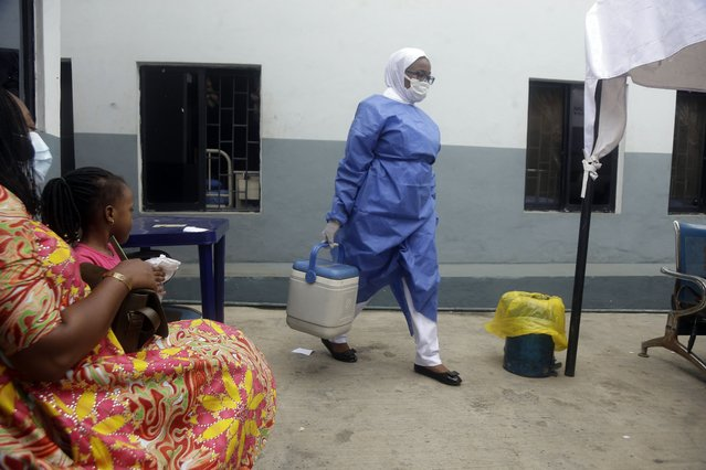 A nurse carries a box containing Moderna vaccines at the health center in Lagos, Nigeria Wednesday, August 25, 2021. Nigeria has begun the second rollout of COVID-19 vaccines as it aims to protect its population of more than 200 million amid an infection surge in a third wave of the pandemic. (Photo by Sunday Alamba/AP Photo)