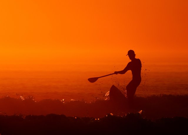 A man on a paddle board surfs during sunset at La Torche, as a heat wave hits France, in Plomeur, Brittany, France, September 6, 2021. (Photo by Pascal Rossignol/Reuters)