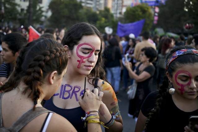 "A woman writes the word ""Free"" on her friend at an event marking International Women's Day in Santiago, Chile, Thursday, March 8, 2018. Many women stayed home from work, joined rallies or wore red Wednesday as International Women's Day was observed with a multitude of events around the world. (Photo by Esteban Felix/AP Photo)"