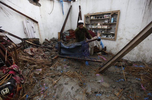A man collects belongings from his home following torrential rains in Peshawar, Pakistan, 27 April 2015. (Photo by Bilawal Arbab/EPA)