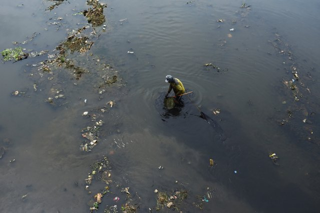 A man fishes using a net in a polluted river in Bandung, West Java on September 13, 2021. (Photo by Timur Matahari/AFP Photo)