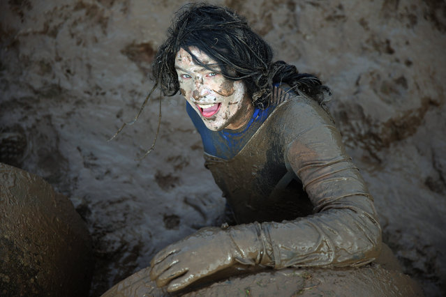 A competitor pulls herself out of a tunnel during the Tough Guy Challenge on January 26, 2014 in Telford, England. (Photo by Bryn Lennon/Getty Images)