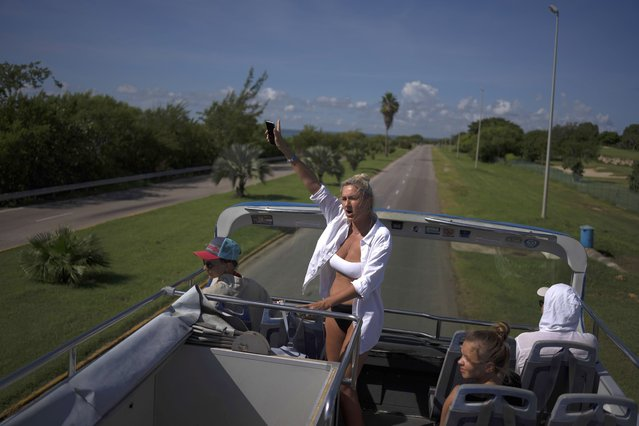 Russian tourists wave from a tour bus while on a city tour of Varadero, Cuba, Wednesday, September 29, 2021. Authorities in Cuba have begun to relax COVID restrictions in several cities like Havana and Varadero. (Photo by Ramon Espinosa/AP Photo)