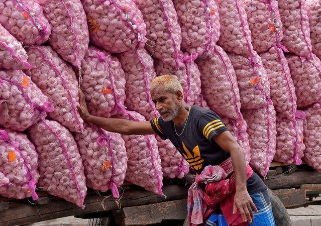 A labourer pushes a handcart loaded with garlic sacks at a wholesale market in Kolkata, India, January 28, 2019. (Photo by Rupak De Chowdhuri/Reuters)