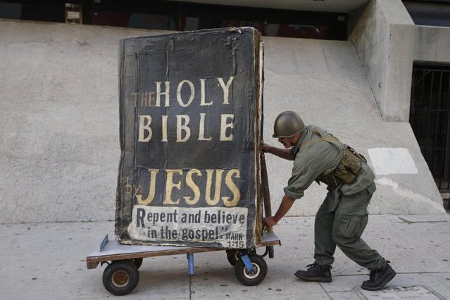 Isidro Mendoza, 39, who calls himself an evangelist, pushes a cart with a large Bible on it, Tuesday, April 28, 2015, in Los Angeles. (Photo by Jae C. Hong/AP Photo)