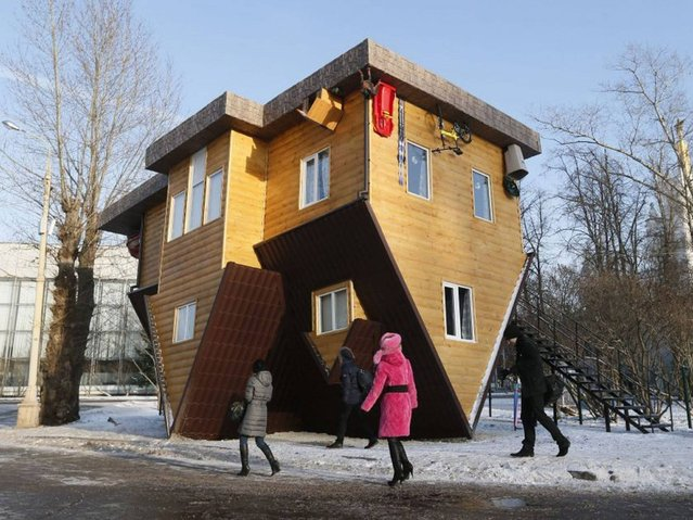 "People look at an ""Upside Down House"" attraction displayed at the VVTs the All-Russia Exhibition Center in Moscow. (Photo by Yuri Kochetkov/EPA)"