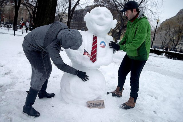 """Daphne Kiplinger and her husband Dave Steadman sculpt a """"Snowbama"""" in Dupont Circle in Washington, DC. Up to 12 inches of snow fell over the Washington area, causing WMATA to cancel bus service. (Photo by Chip Somodevilla/Getty Images)"""