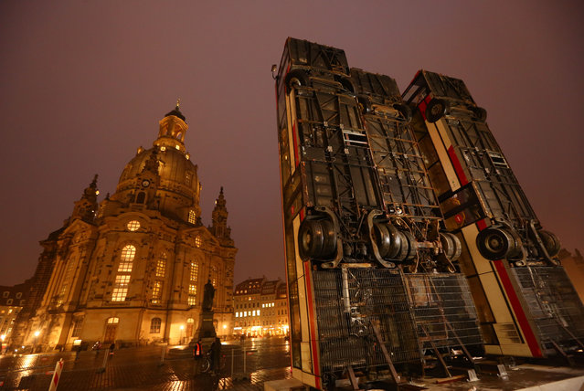 """The artwork """"Monument"""" from the Syrian artist Manaf Halbouni is made of three vertically erected busses and can be seen at the Neumarkt in Dresden, Germany, 7 February 2017. The art should serve as a reminder of the pain and suffering people have endured in the city Aleppo in Syria. It will remain on the Neumarkt for two months, as part of the memorial of the destruction of Dresden during the second world war. (Photo by Action Press/Rex Features)"""