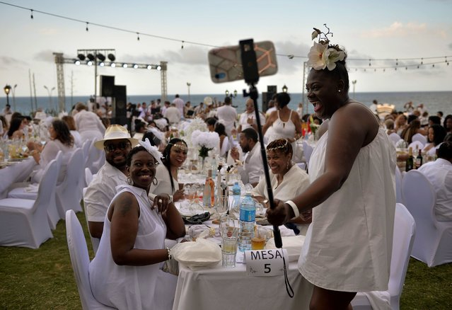 """Guests in white costumes pose for a selfie during the """"Diner en Blanc"""" event, at the Hotel Nacional in Havana on April 6, 2019. (Photo by Yamil Lage/AFP Photo)"""