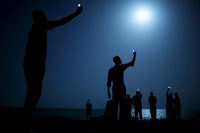 World Press Photo of the Year 2013. John Stanmeyer, USA, VII for National Geographic. The photo shows African migrants on the shore of Djibouti city at night, raising their phones in an attempt to capture an inexpensive signal from neighboring Somalia in Djibouti City, Djibouti, February 26, 2013. (Photo by John Stanmeyer/World Press Photo)